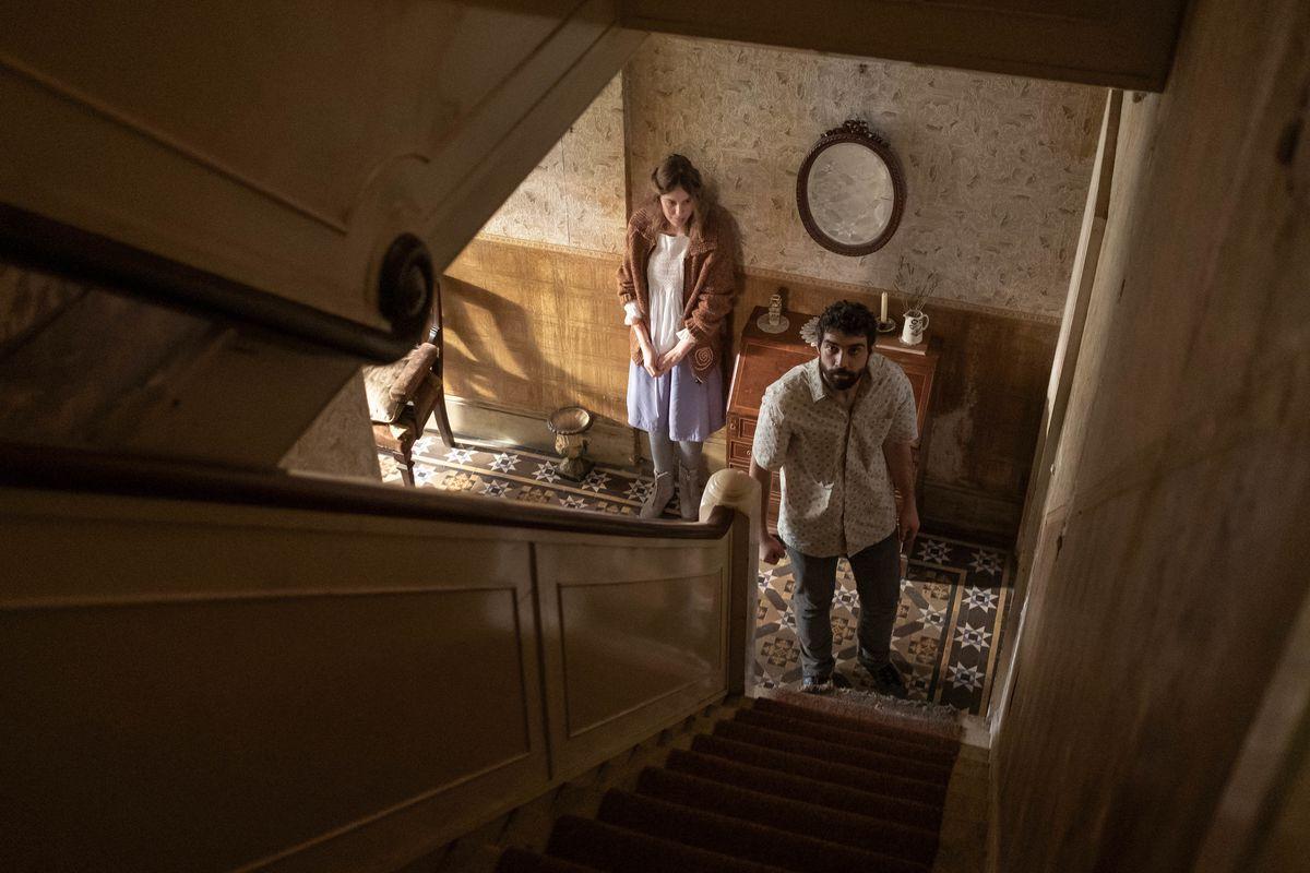 Deux personnes au bas d'un escalier, levant les yeux, dans le film d'horreur de Romola Garai Amulet.