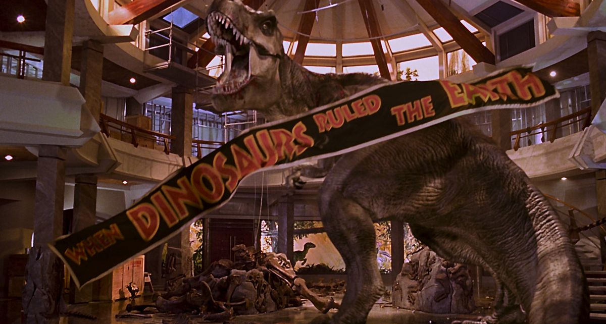 "jurassic park ending: the t-rex defeats the raptors in the jurassic park lobby as a ""when the dinosaurs ruled the earth"" banner falls from the ceiling"