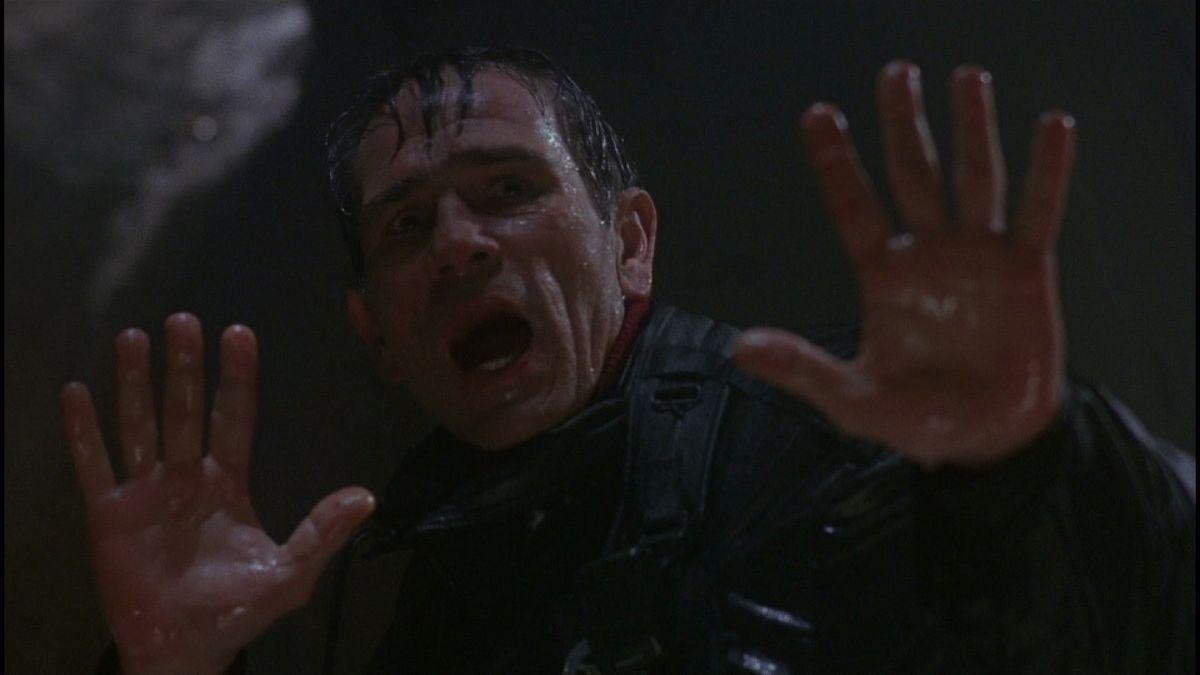 Un homme imbibé d'eau lève les mains.