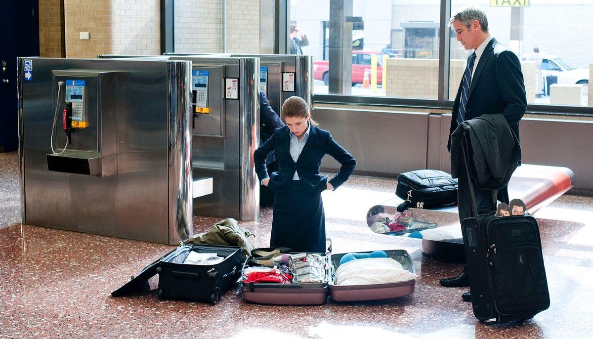 Anna Kendrick s'agenouille devant ses bagages écartés dans un aéroport de Up in the Air, tandis que George Clooney la regarde.