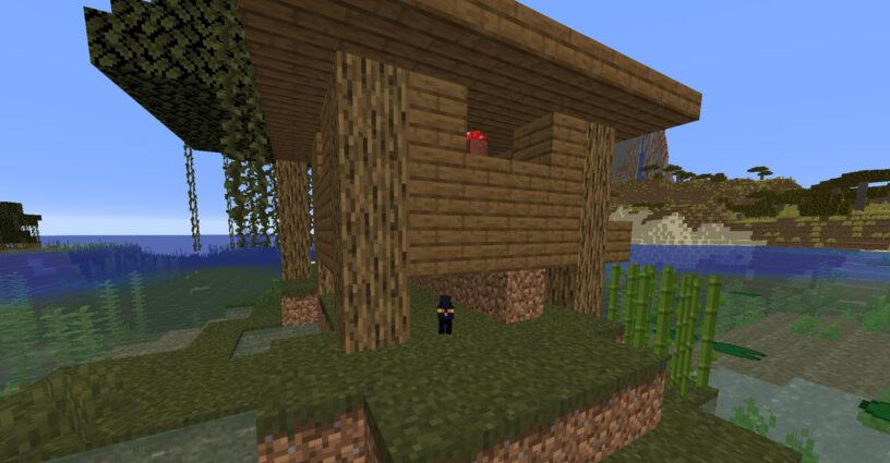 Chat noir sous une hutte de sorcière dans Minecraft