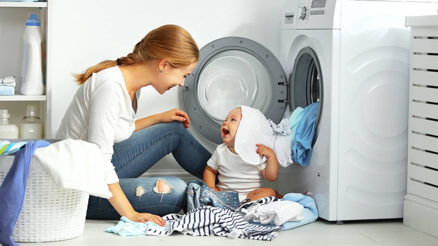 Mère lave les vêtements avec bébé ensemble