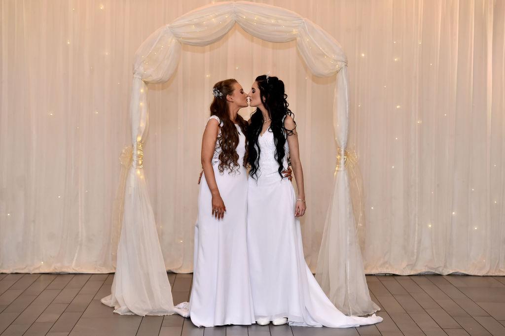Robyn Peoples et Sharni Edwards s'embrassent après être devenus le premier couple de même sexe légalement marié en Irlande du Nord le 11 février 2020 à Carrickfergus, en Irlande du Nord.