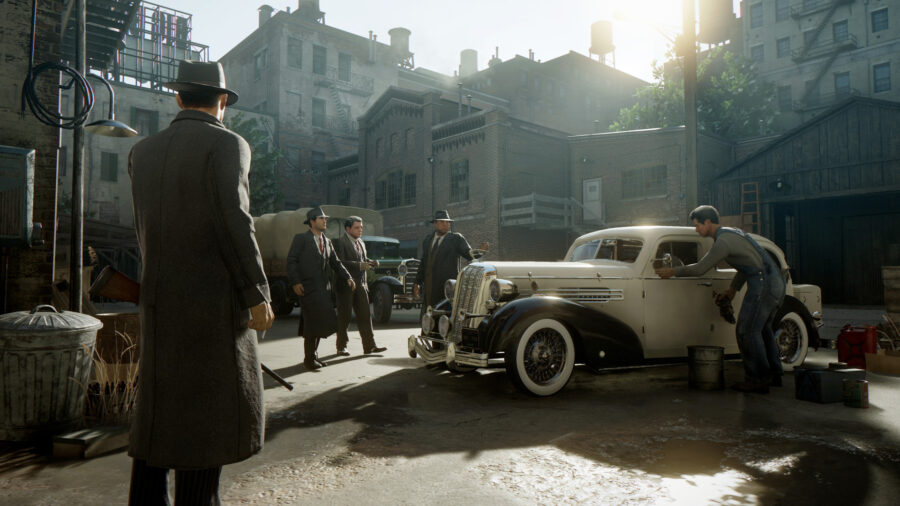 Une capture d'écran de Mafia: Definitive Edition.  Les gars de la mafia traînant autour d'une voiture