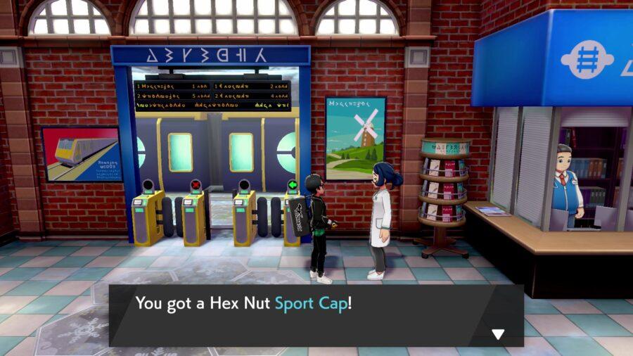 Une capture d'écran de la femme scientifique de la station Crown Tundra qui vous donne la casquette Hex Nut Sport Cap pour lui avoir montré un certain Pokémon - Meltan ou Melmetal