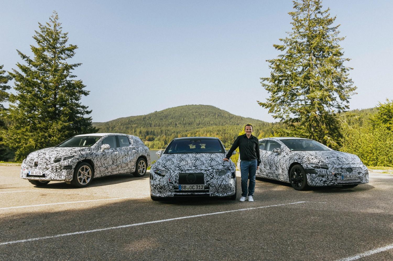 La Mercedes EQE Saloon, EQE SUV et EQS SUV, tous encore camouflés, flanqués du vice-président de la marque pour la gamme EQ, Christoph Starzynski