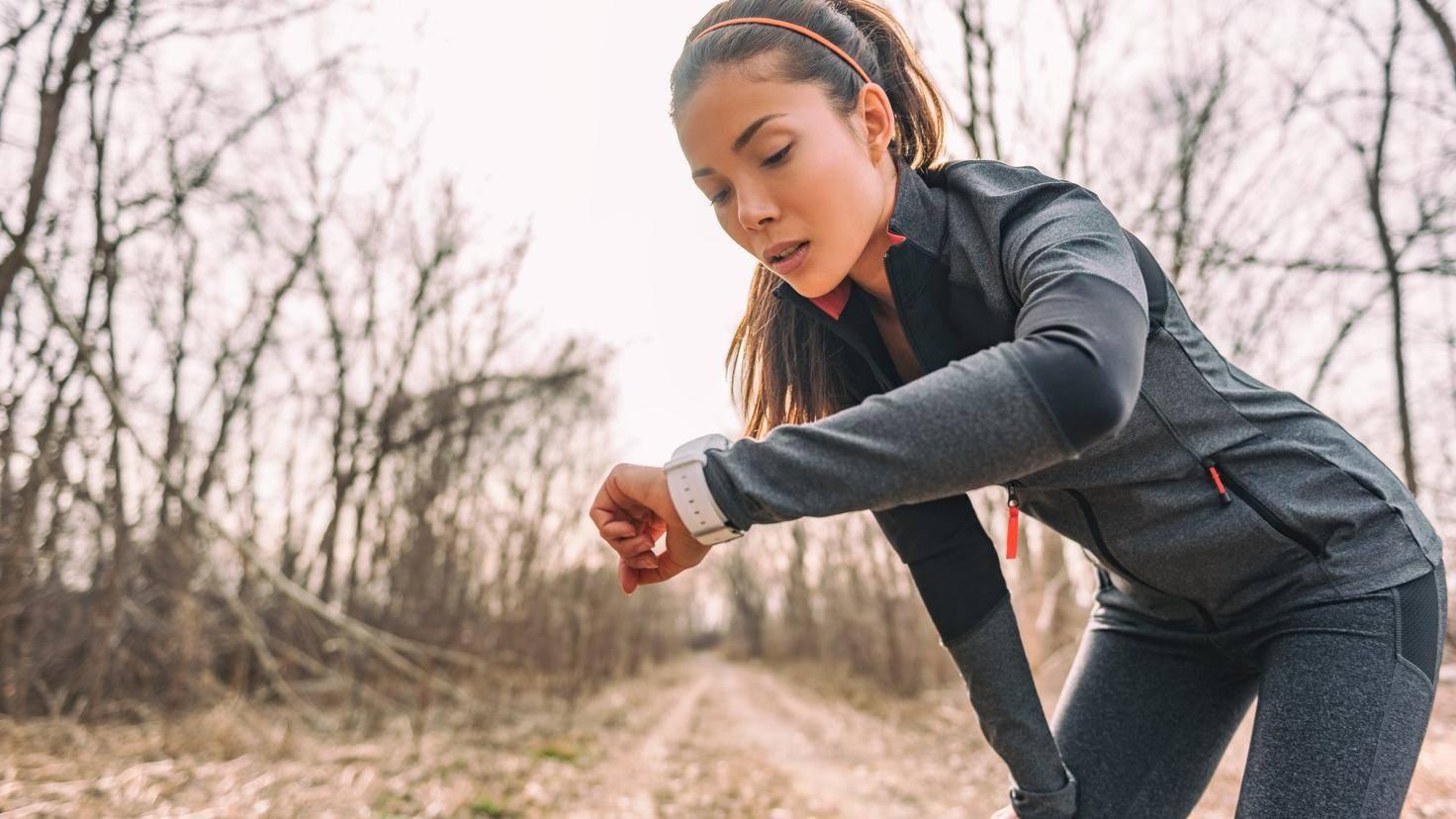 Jogger regarde sa montre intelligente tout en faisant de l'exercice