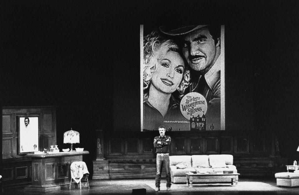 Burt Reynolds parle sur scène avec une image de lui et de Dolly Parton