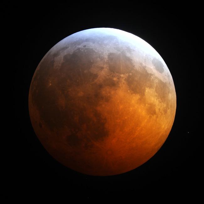 Cette photo de l'éclipse lunaire totale du 20 décembre 2010 par Jimmy Westlake montre le bord bleu de l'ombre de la Terre sur la lune rougie.