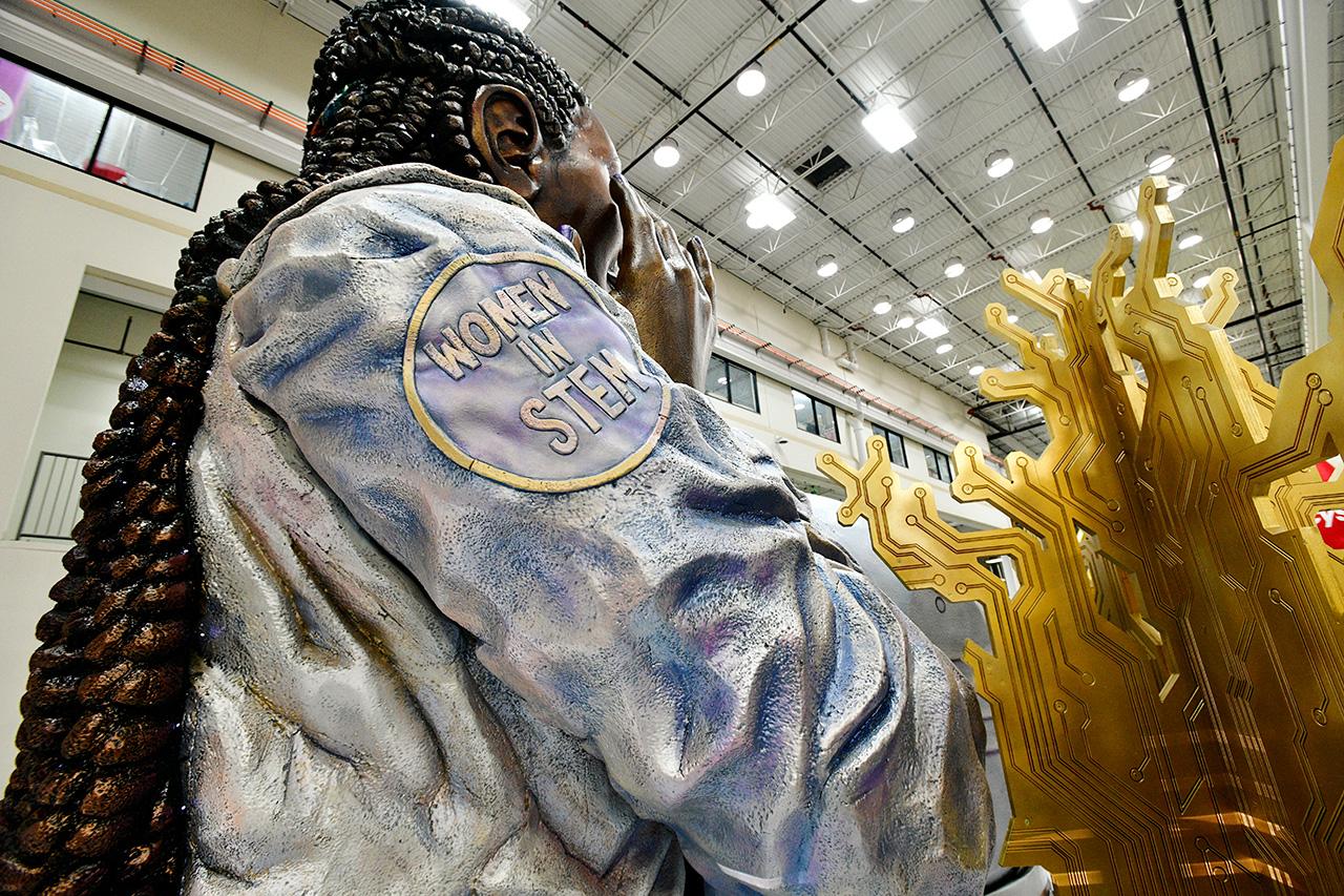 """La femme astronaute sur le char de la parade de Thanksgiving 2020 d'Olay Macy porte une veste avec des écussons de mission qui indiquent """"Femmes en STEM,"""" symbolisant l'objectif sur 10 ans de la marque d'aider à doubler le nombre de femmes dans les STEM et à tripler le nombre de femmes multiculturelles dans les domaines des sciences et des technologies."""