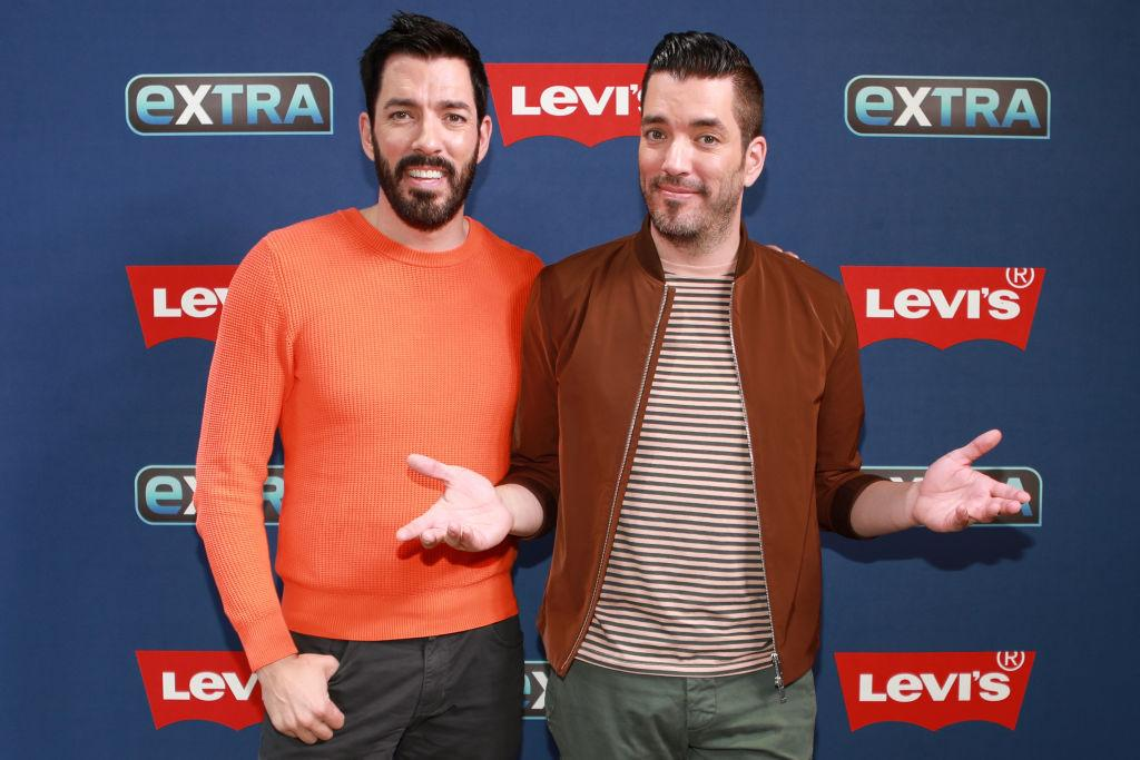 (L-R) Drew Scott and Jonathan Scott smiling in front of a blue background