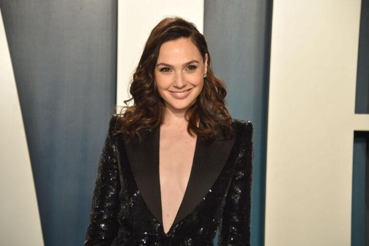 Gal Gadot smiling in front of a blue background