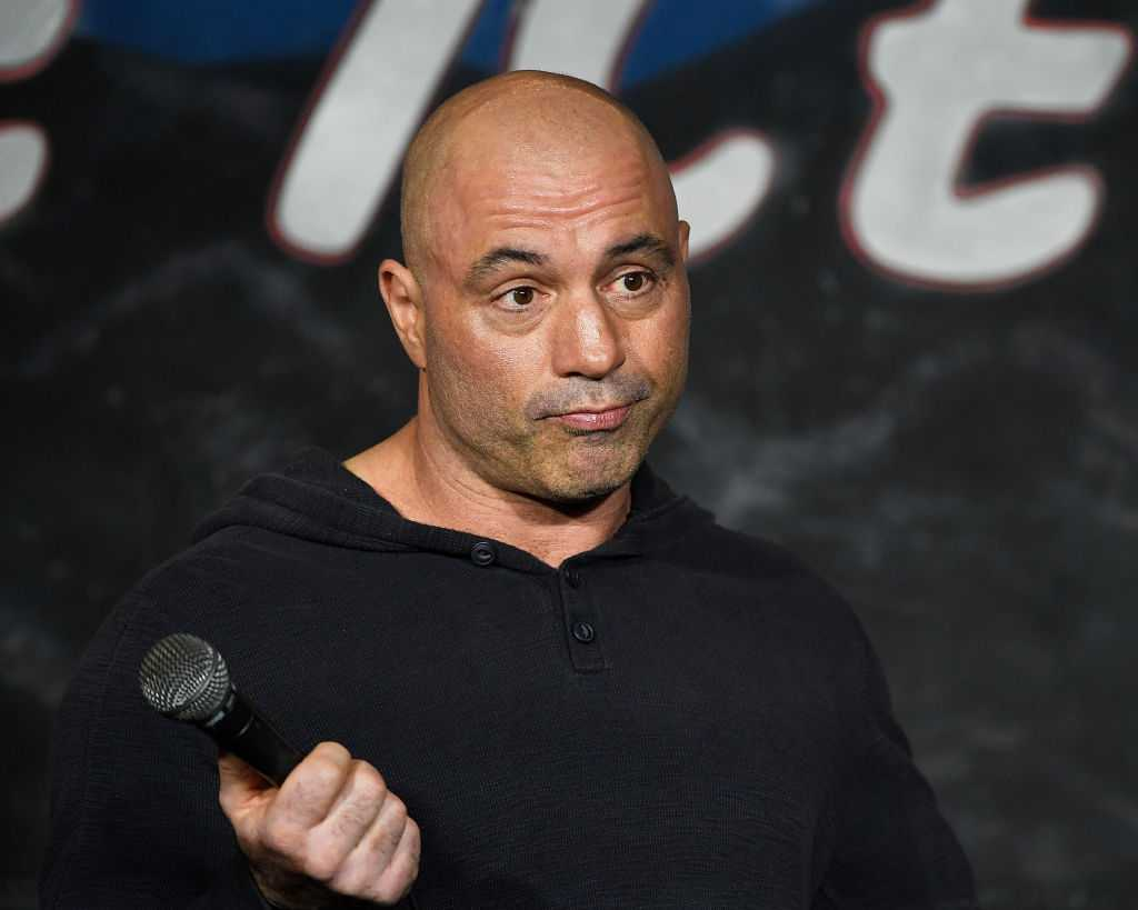 Joe Rogan shrugging, holding a microphone