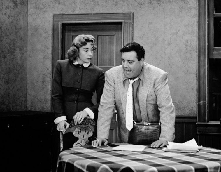 Audrey Meadows as Alice Kramden and Jackie Gleason as Ralph Kramden stand in the kitchen on the set of