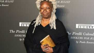Whoopi Goldberg smiling slightly in front of a black background