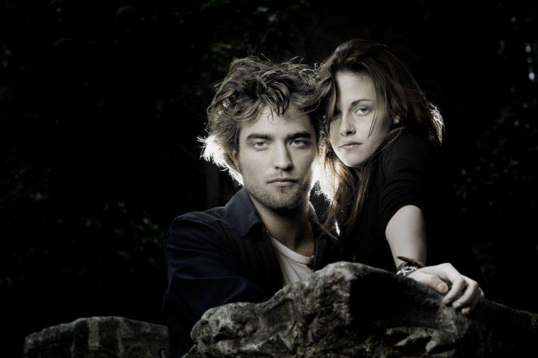 Robert Pattinson and Kristen Stewart near a rock in a Twilight promotional image