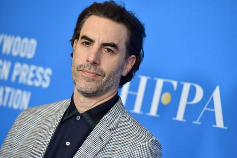 Sacha Baron Cohen smiling slightly in front of a blue background