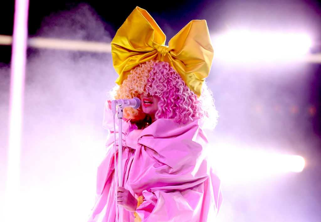 Sia wearing a curly pink wig and yellow bow performing on stage