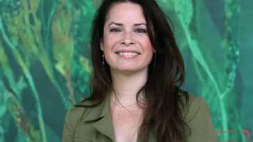 Holly Marie Combs smiling in front of a green background