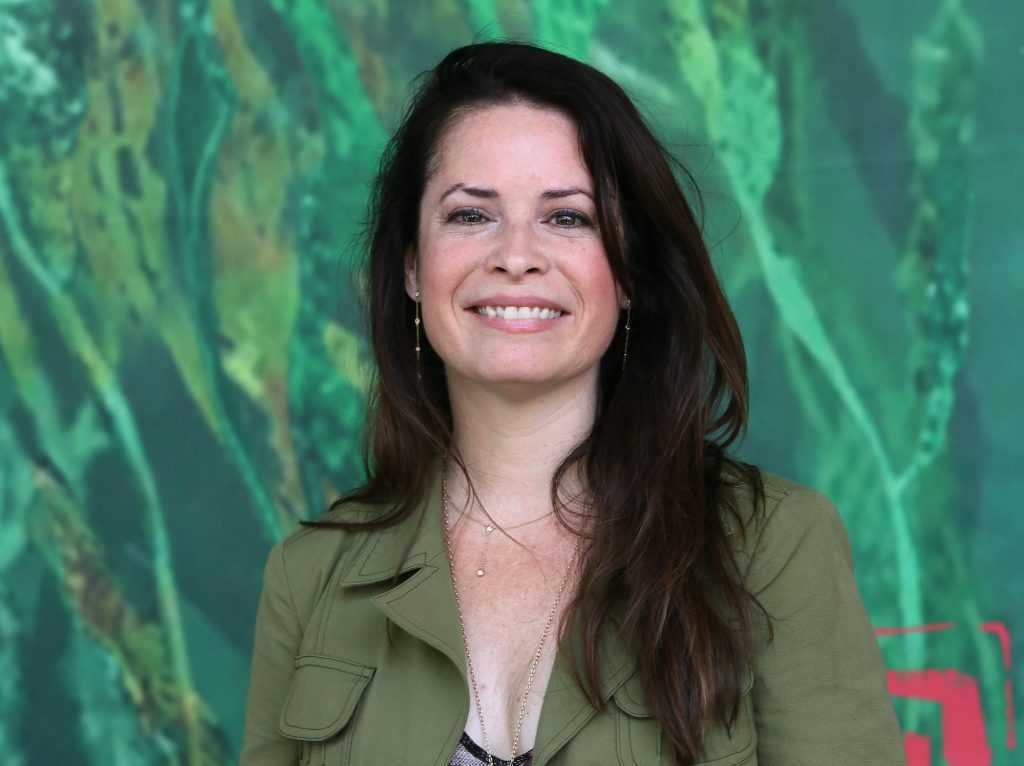 Holly Marie Combs souriant devant un fond vert