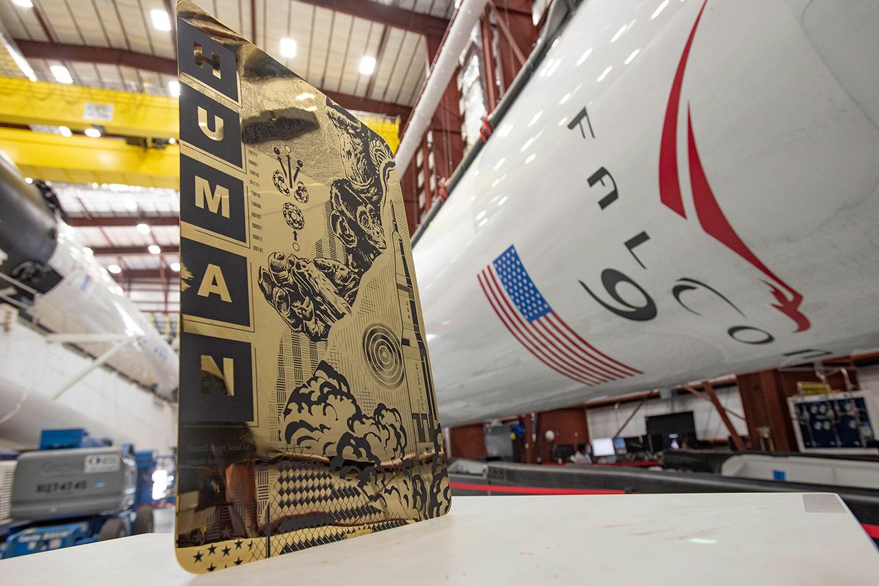 """Tristan Eaton """"Genre humain"""" artwork, vu à côté des fusées SpaceX Falcon 9 au centre spatial Kennedy de la NASA en Floride."""