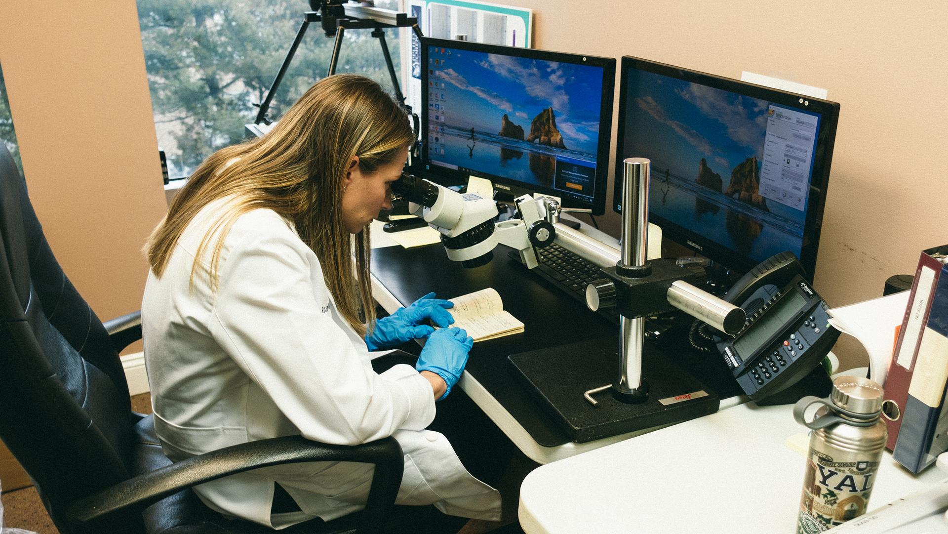 Jennifer Naso, examinatrice de documents médico-légaux, inspecte le journal du major Marcel à l'aide d'un comparateur spectral vidéo.