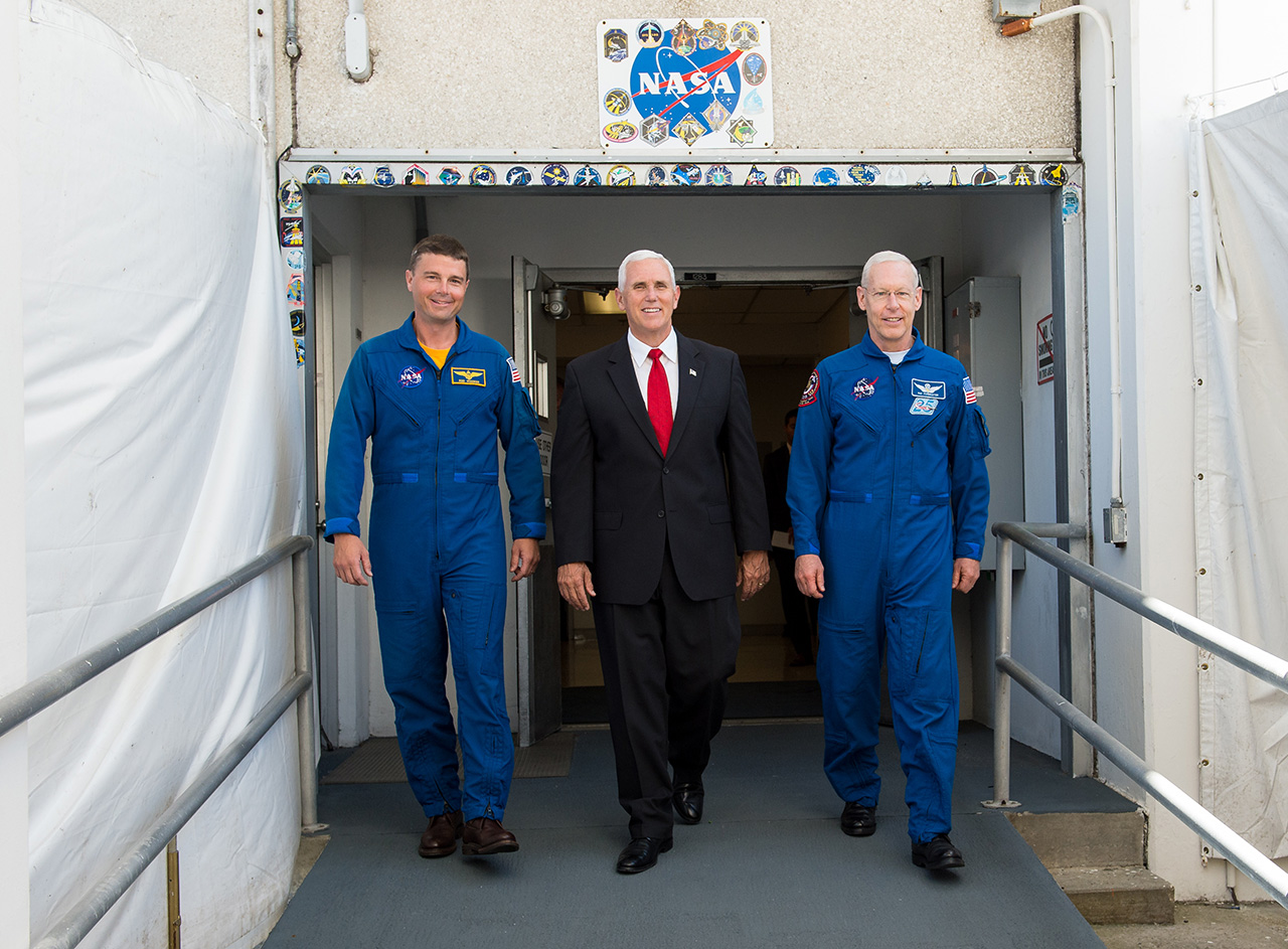 Les astronautes en chef entrants et sortants de la NASA, Reid Wiseman (à gauche) et Patrick Forrester (à droite) accompagnent le vice-président Mike Pence hors du bâtiment Neil A. Armstrong Operations & Checkout au Kennedy Space Center en juillet 2017.