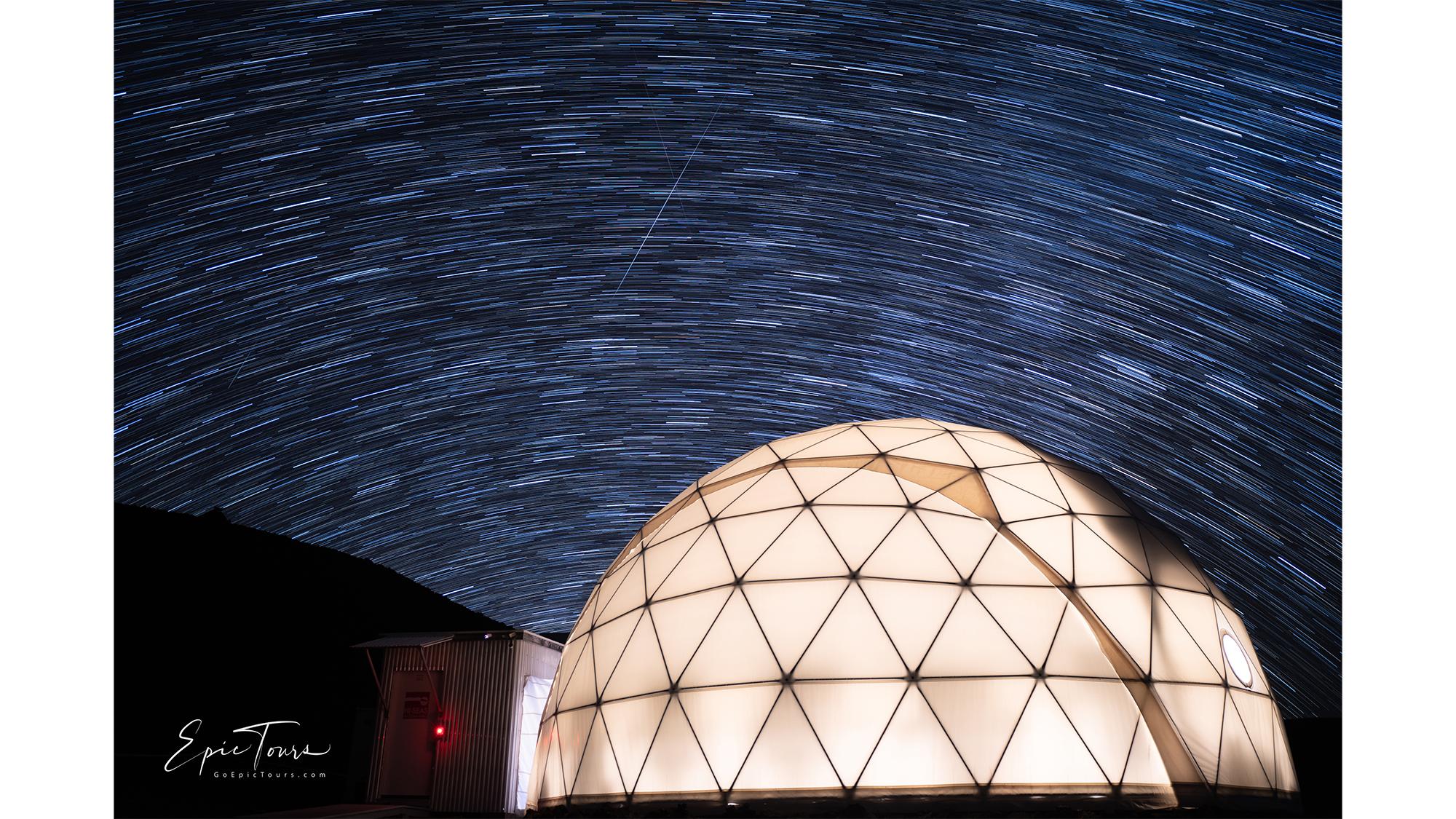 Des traînées d'étoiles et des étoiles filantes illuminent le ciel nocturne au-dessus de l'habitat HI-SEAS.
