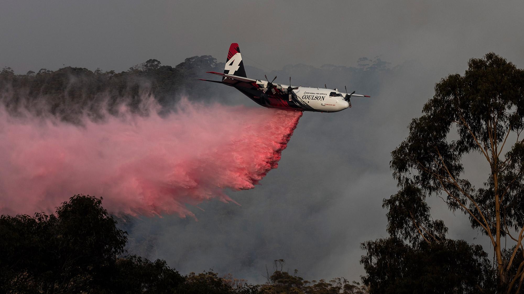 Image d'hélicoptère libérant un retardateur de flamme sur un feu de brousse australien