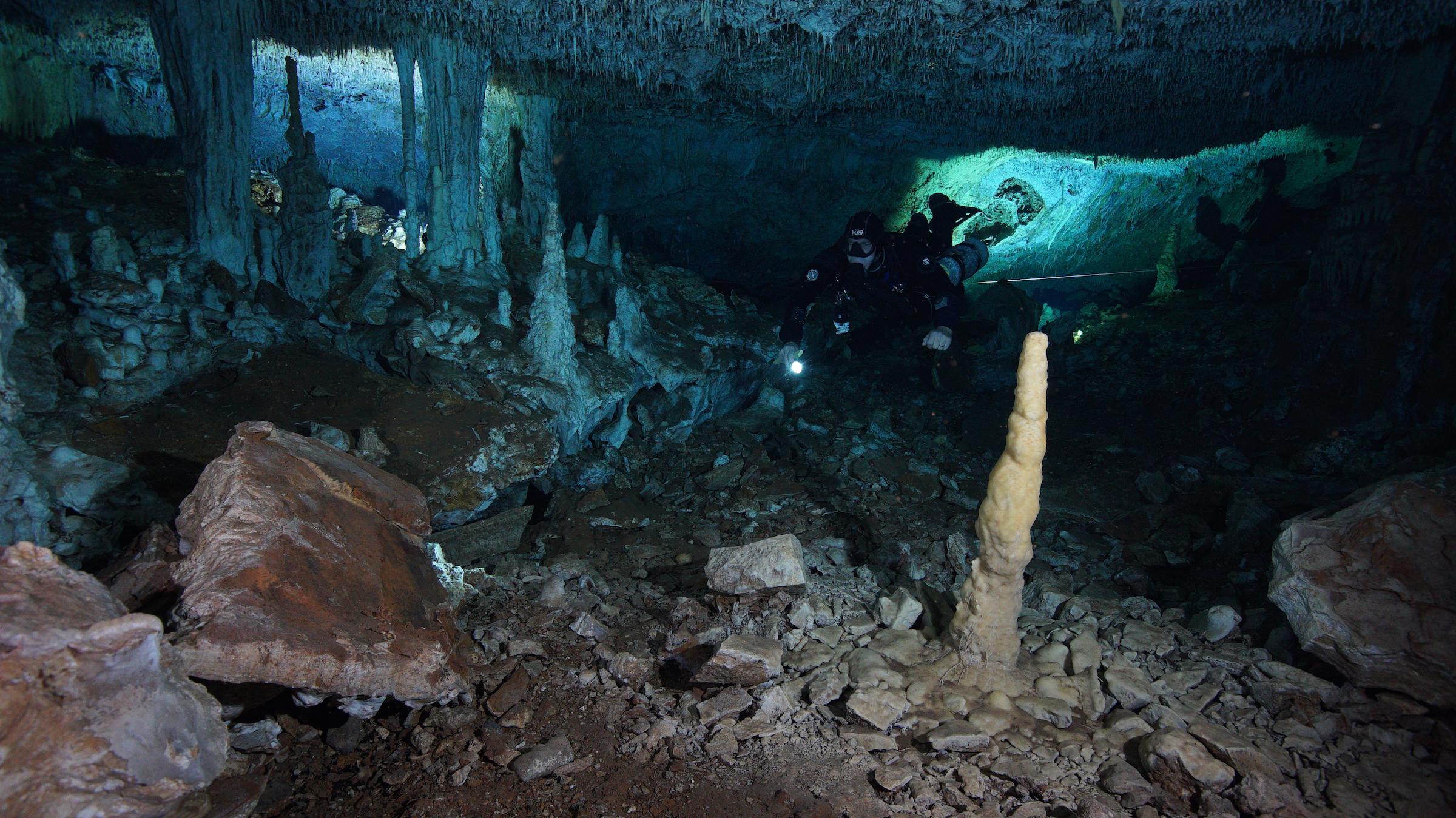 Avec seulement une lampe de poche pour éclairer le chemin, un plongeur CINDAQ explore l'ancienne mine d'ocre.  À la fin de la dernière période glaciaire, ces grottes étaient sèches, mais auraient été dépourvues de toute lumière naturelle.