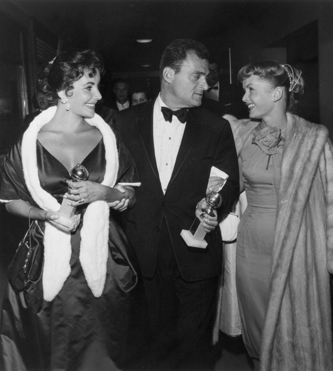 De gauche à droite, l'acteur d'origine britannique Elizabeth Taylor et son mari, le producteur de cinéma Mike Todd (1909-1958), décernent leurs Golden Globe Awards en marchant avec l'acteur américain Debbie Reynolds au dîner de remise des prix de la Hollywood Foreign Press Association à Los Angeles.  Taylor a remporté un prix spécial pour ses performances constantes et Todd a produit le film de Michael Anderson en 1957, «Autour du monde en quatre-vingt jours», qui a reçu le prix du meilleur film dramatique.