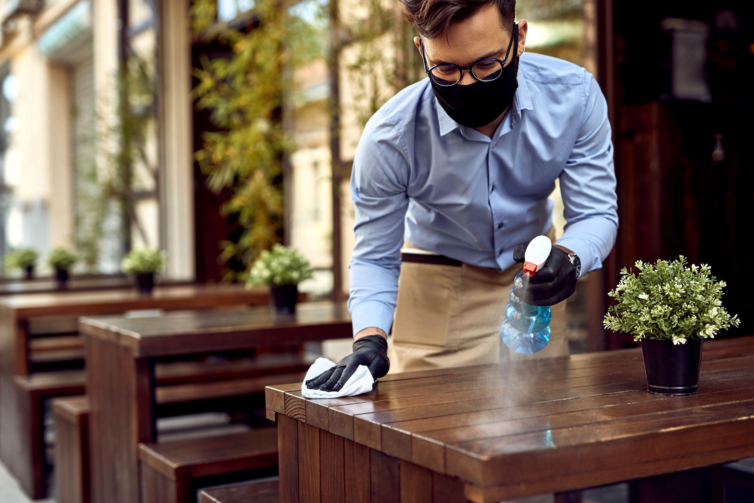 Un travailleur désinfectant les tables dans un restaurant.