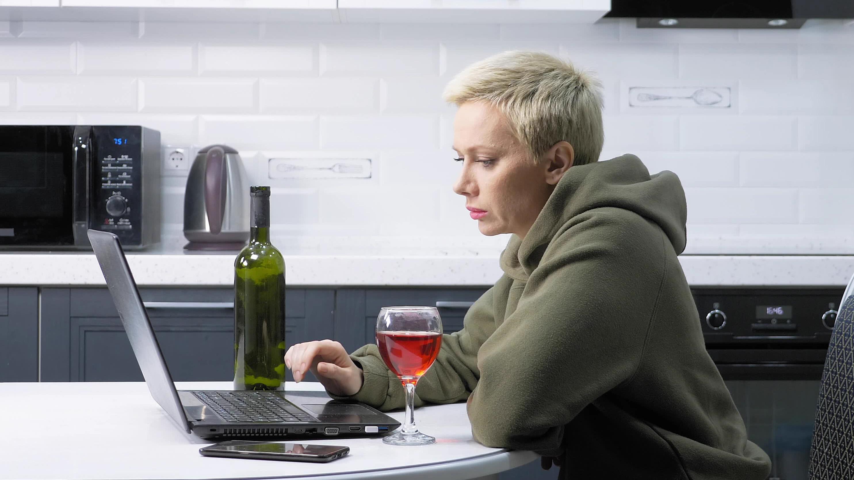 Une femme utilise un ordinateur portable et boit du vin dans la cuisine.