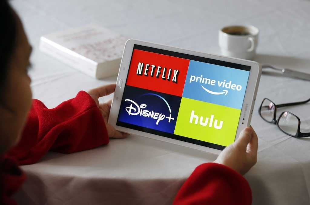 In this photo illustration, the logos of media service providers, Netflix, Amazon Prime Video, Disney + and Hulu are displayed on the screen of a tablet.