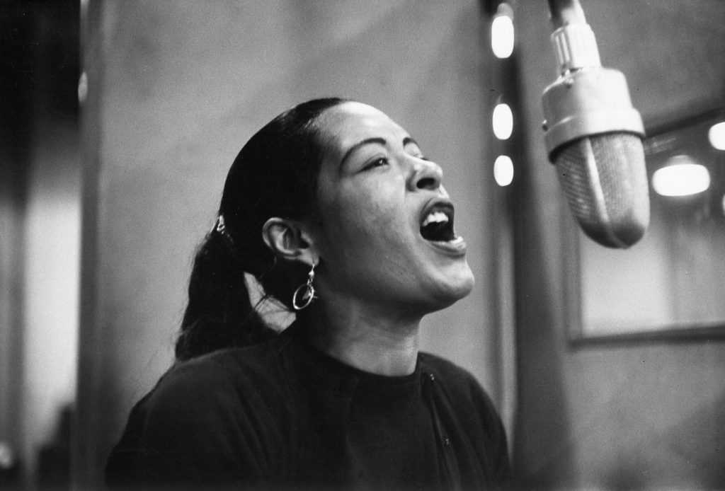 Billie Holiday singing into a microphone