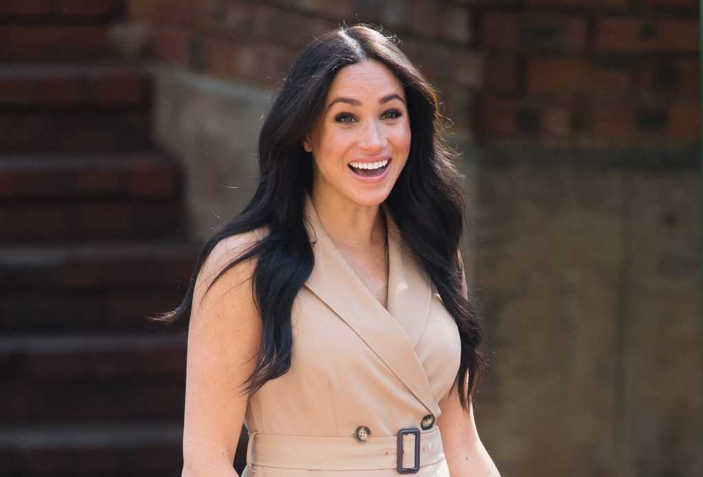 Meghan Markle smiling in front of a brick building