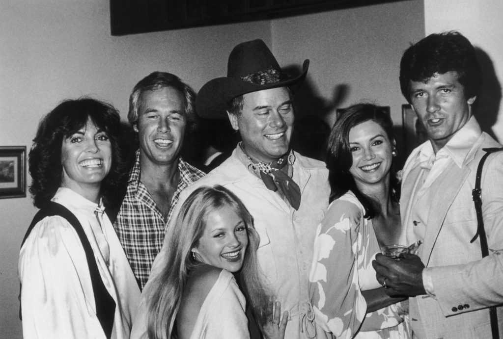 (L-R) Linda Gray, Steve Kanaly, Charlene Tilton, Larry Hagman, Victoria Principal and Patrick Duffy smiling, in black and white