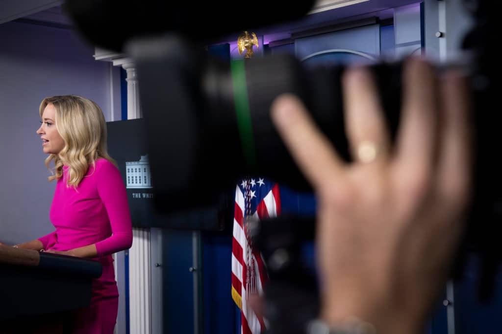 Kayleigh McEnany prend la parole dans une robe rose derrière le podium de presse de la salle de briefing de la Maison Blanche