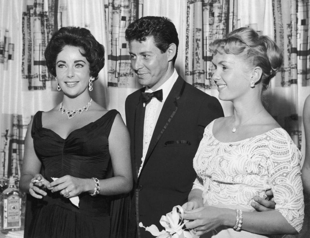 Le chanteur américain Eddie Fisher, vêtu d'un smoking, se tient avec le bras autour de sa femme, l'acteur américain Debbie Reynolds (R) et sourit tout en regardant l'acteur d'origine britannique Elizabeth Taylor, fumant une cigarette, Las Vegas, Nevada.  L'année suivante, Fisher quitta Reynolds et épousa Taylor.