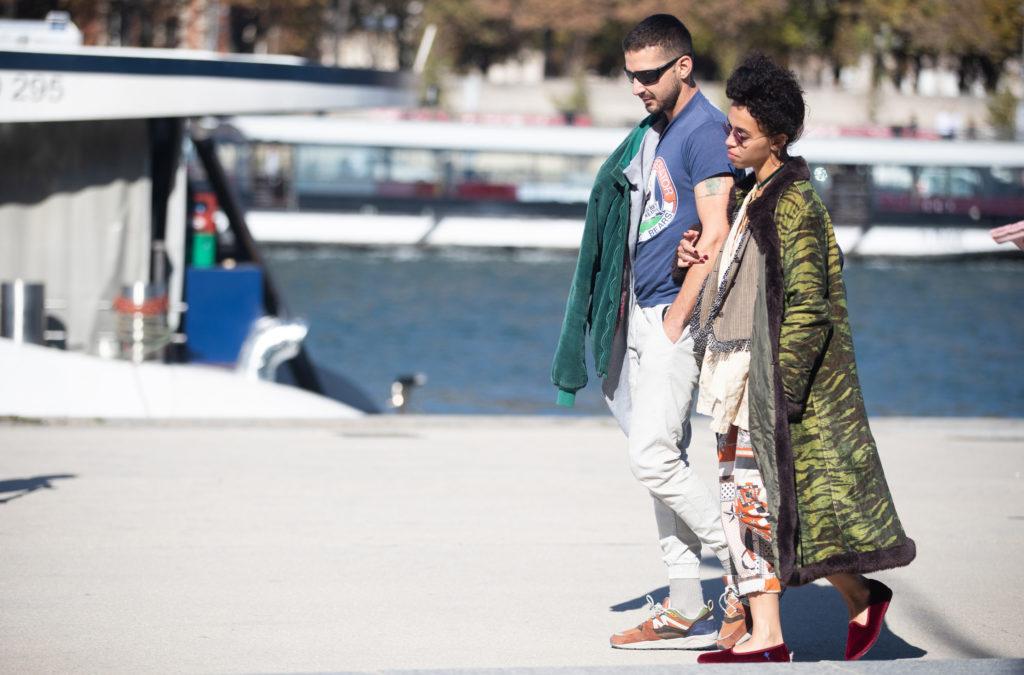 Shia LaBeouf et FKA Twigs marchent le long d'une jetée avec un bateau derrière eux