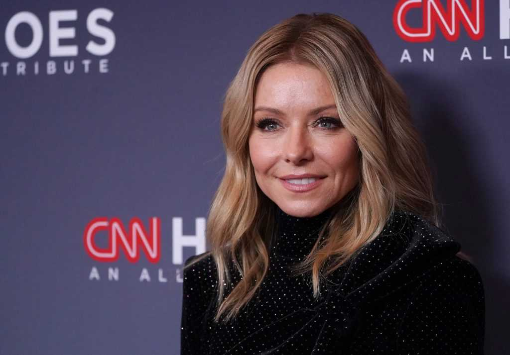 Kelly Ripa smiling in front of a blue background