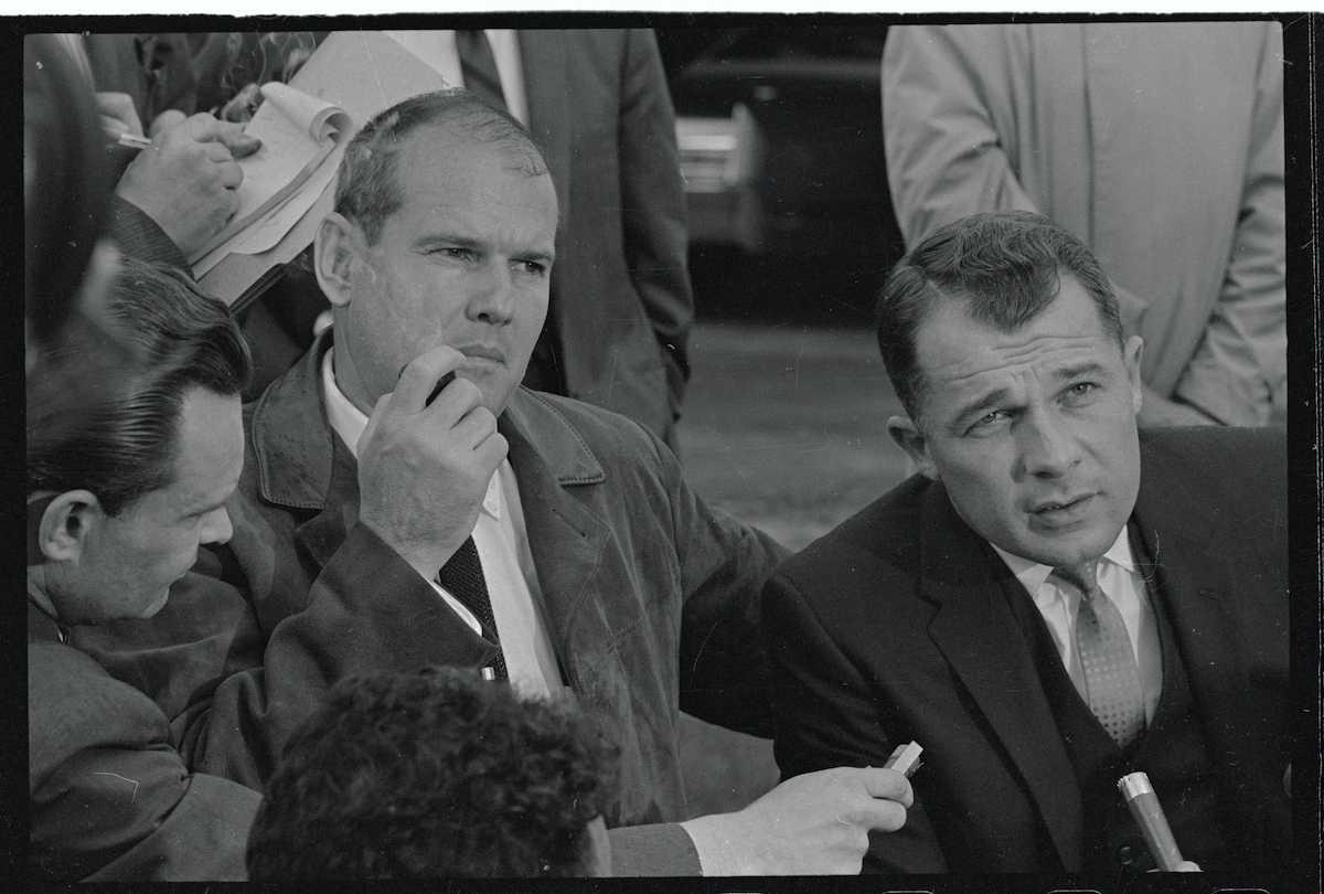 Le Dr Samuel Sheppard écoute son avocat, F. Lee Bailey, répondre aux questions des hommes de presse devant la maison du frère de Sheppard, Richard