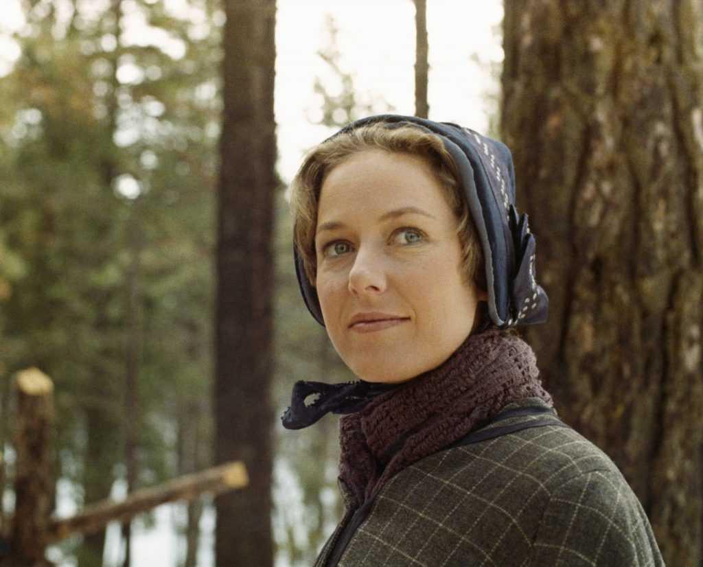 Karen Grassle as Caroline Quiner Holbrook Ingalls smiling in front of a tree