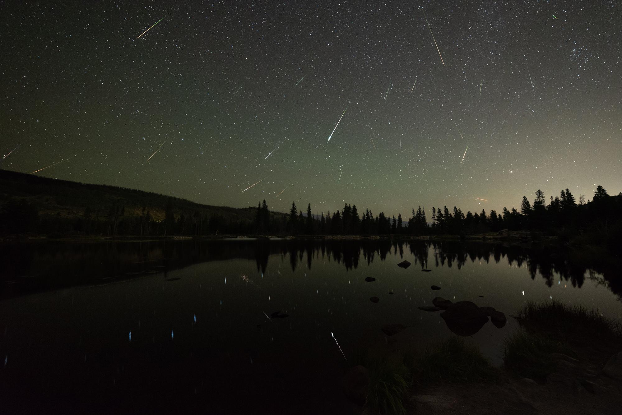 De nombreux météores - y compris des boules de feu - sont visibles sur le lac Sprague dans le parc national des montagnes Rocheuses sur cette photo de l'astrophotographe Sergio Garcia Rill.  Il a capturé ces météores au pic de la pluie de météores perséides le 12 août 2018.
