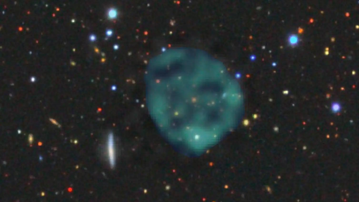 L'ORC1 fantomatique (fuzz bleu / vert), sur fond de galaxies aux longueurs d'onde optiques.  Il y a une galaxie orange au centre de l'ORC, mais nous ne savons pas si elle fait partie de l'ORC, ou simplement une coïncidence fortuite.