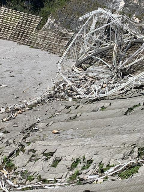 Dommages subis au télescope de 305 mètres de l'observatoire d'Arecibo.  La partie supérieure des trois tours de support du télescope s'est rompue.  Lorsque la plate-forme d'instruments de 900 tonnes est tombée, les câbles de support du télescope ont également chuté.