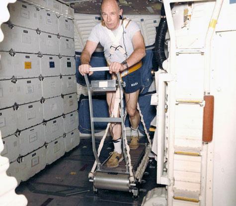 L'astronaute de la NASA Bill Thornton travaille avec le tapis roulant qu'il a inventé pour être utilisé à bord de la navette spatiale.