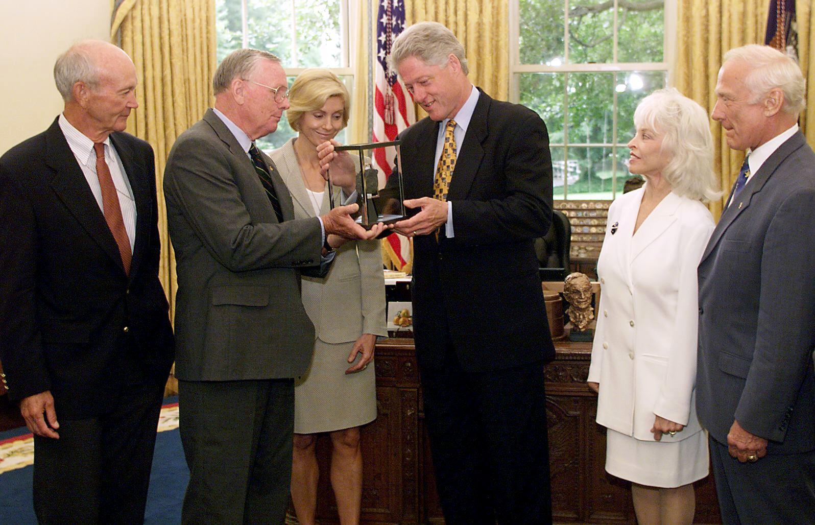 Le président Bill Clinton (au centre) reçoit un rocher lunaire par l'astronaute d'Apollo 11 Neil Armstrong et sa femme, Carol Armstrong, aux côtés des coéquipiers d'Apollo 11 Michael Collins (extrême gauche) et Buzz Aldrin (à droite) et de sa femme Lois Aldrin, dans le bureau ovale sur 20 juillet 1999.