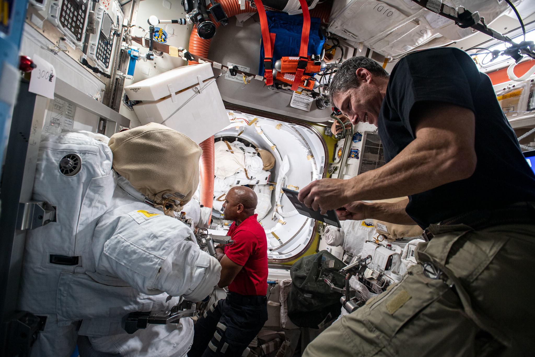Les astronautes de la NASA Mike Hopkins (au premier plan) et Victor Glover configurent des outils à l'intérieur du sas Quest de la Station spatiale internationale le 8 janvier 2021, pour se préparer à deux sorties dans l'espace prévues.