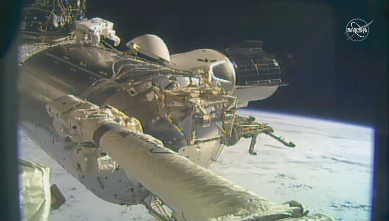 Vue du vaisseau spatial Crew-1 Crew Dragon de SpaceX (à droite) amarré à la Station spatiale internationale.  Le vaisseau spatial a transporté quatre astronautes de l'Expédition 64 à la station en novembre, dont Victor Glover et Michael Hopkins de la NASA, qui ont fait une sortie dans l'espace le 27 janvier 2021.